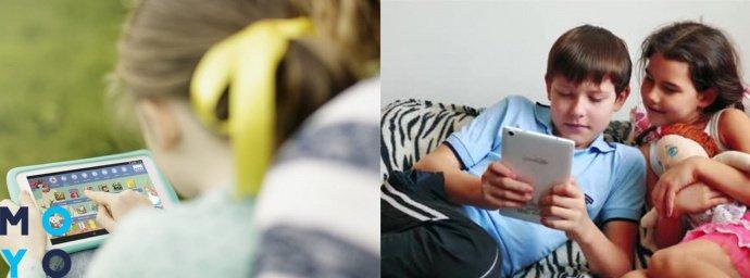 дети играют в планшет, брат учит сестру пользоваться планшетом